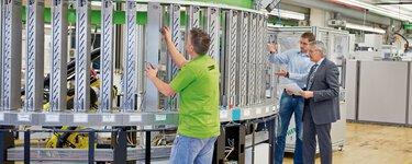 在工廠環境中的人們。一位男士向另一位男士展示和介紹一台機器。