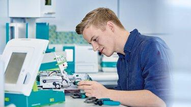 Le service technique répare le système d'impression avec des pièces d'origine de haute qualité