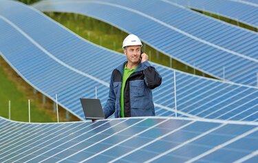 Un technicien au téléphone entre les panneaux d'un parc solaire
