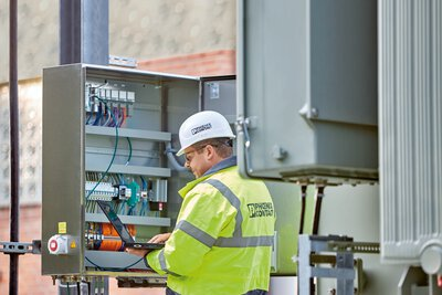 A person is standing in front of the control cabinet at the substation