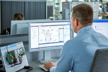 Man in front of a monitor planning plant modules with the MTP Designer software tool