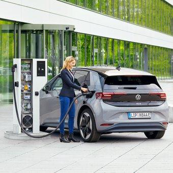 Vrouw steekt laadkabel in elektrische auto