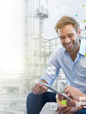 Two men with a tablet in conversation in front of a processing plant