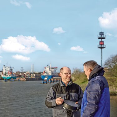 Experts for safe signaling on waterways standing on the waterfront