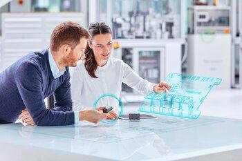 Mitarbeiterin und Kunde betrachten das 3D-Modell eines Steckverbinders