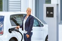 Woman with electric car at a charging station