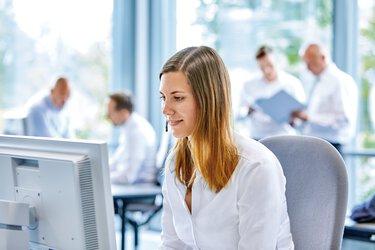 Jeune femme avec casque à l'ordinateur