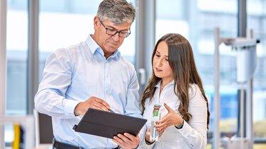 Un collaborateur de Phoenix Contact et une cliente consultent les contenus numériques de Phoenix Contact sur une tablette