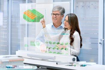 一名員工與一名客戶正在檢視某個連接器的 3D 模型