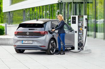 Vrouw laadt elektrische auto op met een laadkabel