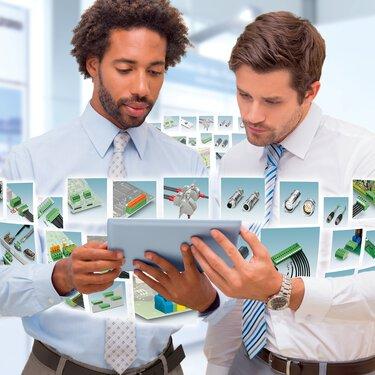 Deux collaborateurs regardent le navigateur de produits sur une tablette, avec diverses superpositions de produits