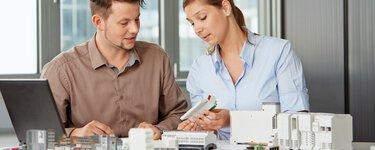 Une jeune femme et un jeune homme discutent de solutions de produits sur la table en face d'eux