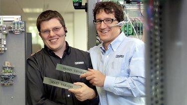 Deux collaborateurs de Phoenix Contact au milieu d'armoires électriques
