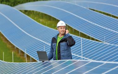 技工正站在太陽能發電廠的太陽能面板之間打電話