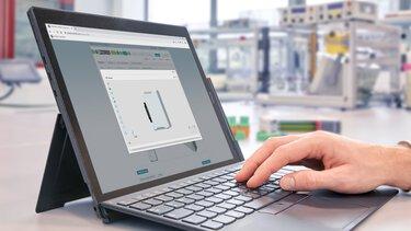 Main sur le clavier d'un écran d'ordinateur portable avec configurateur ouvert