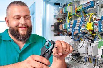電氣安裝期間持有工具的人員在控制櫃前