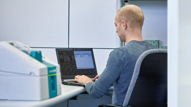 Un collaborateur de l'assistance technique répond à des questions concernant les systèmes de repérage sur un ordinateur portable