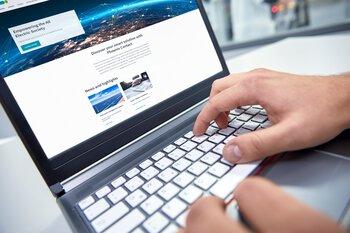 Un homme consulte en ligne sur un ordinateur portable la gamme de produits de PhoenixContact