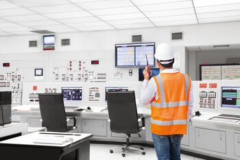 Man in monitoring center with wireless device performing monitoring and diagnostics